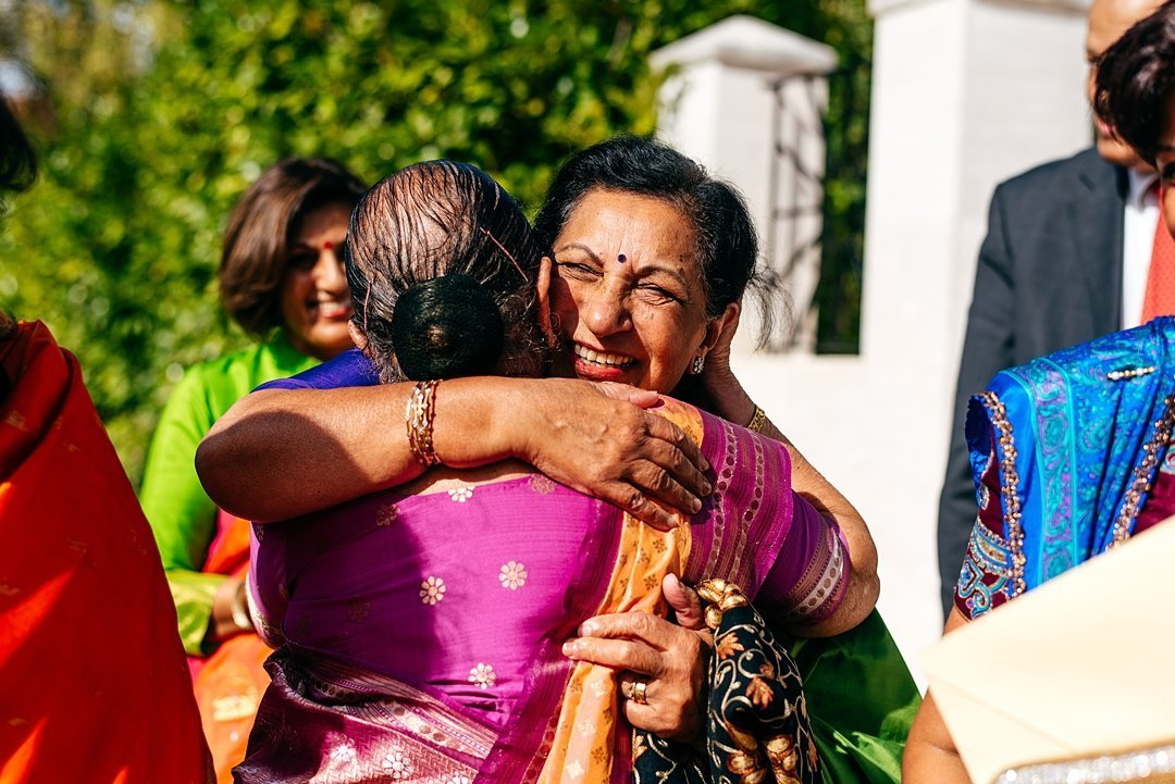 Guest hugs mum of bride at colourful indian wedding