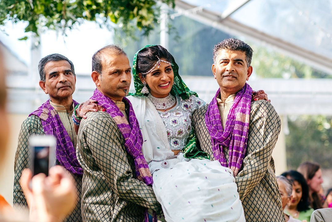 Bride getting really emotional as her uncles carry her to her colourful indian wedding ceremony