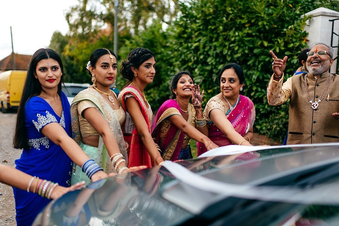 Girls block couples car from leaving in a game as part of colourful indian wedding at home