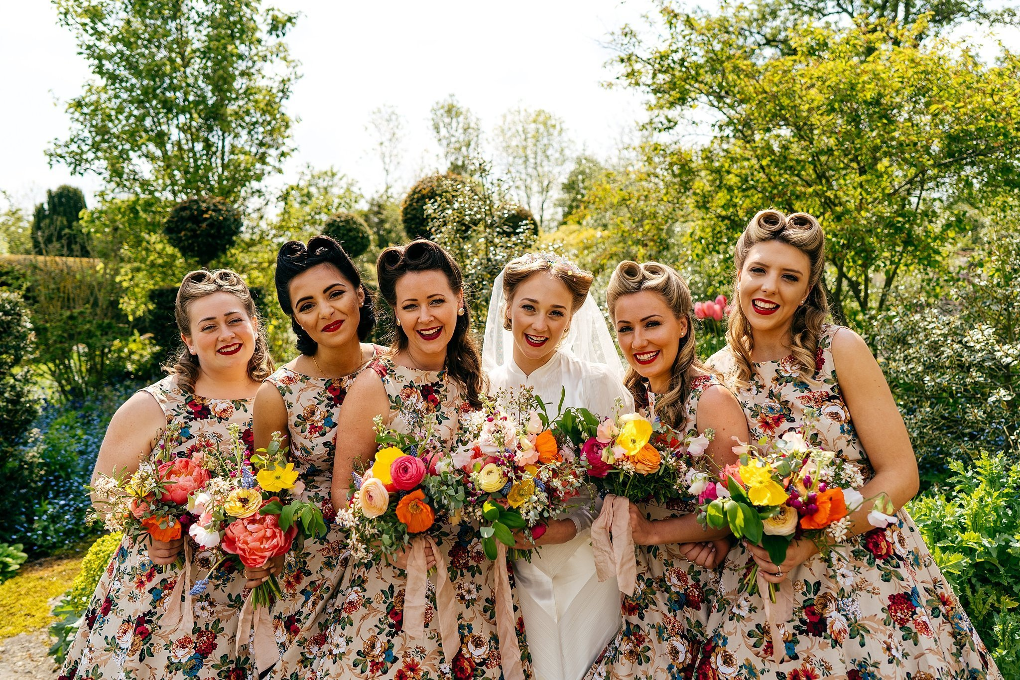 Bride and bridesmaids in Private gardens at Oxleaze Barn Wedding