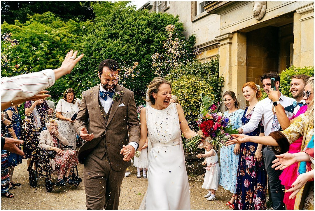 Bride and groom emerge from their Sparkford Hall Wedding ceremony and get scattered with confetti