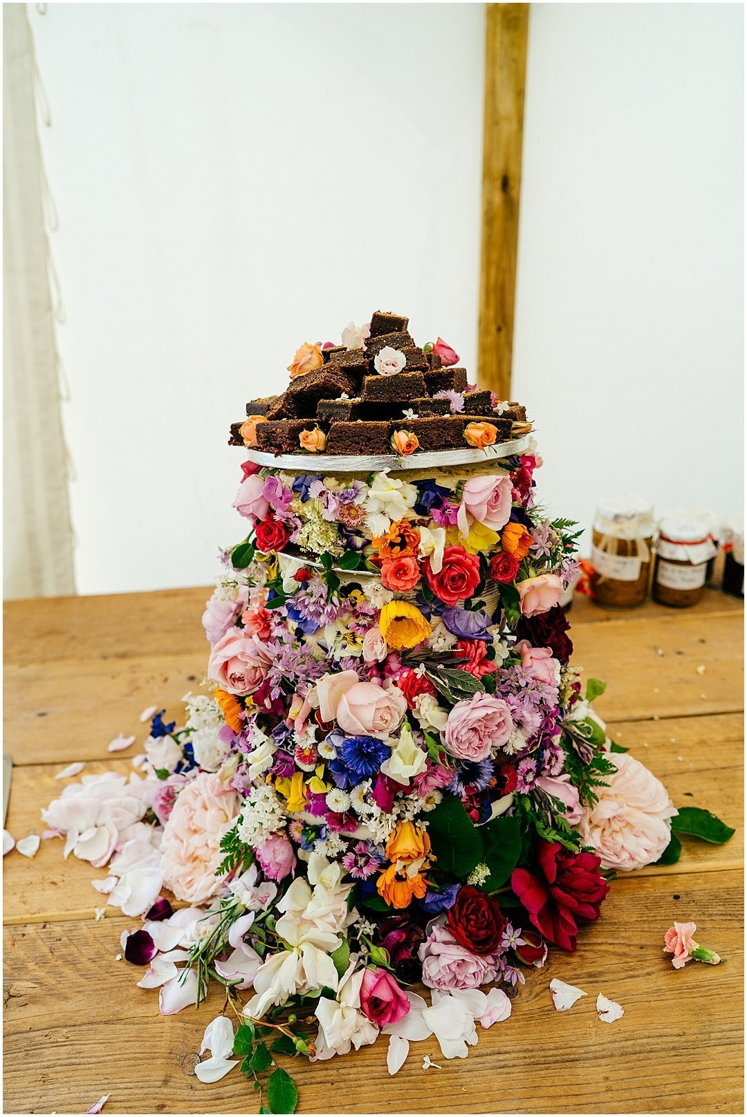 Colourful Wedding Cake with edible flowers at festival wedding at Sparkford Hall