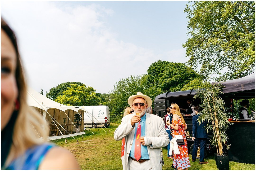 Guest sipping drink from Bar cart at Sparkford Hall festival style wedding