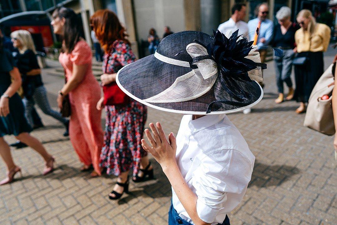 Boy in Grandma's wedding hat walking through the streets of Brighton