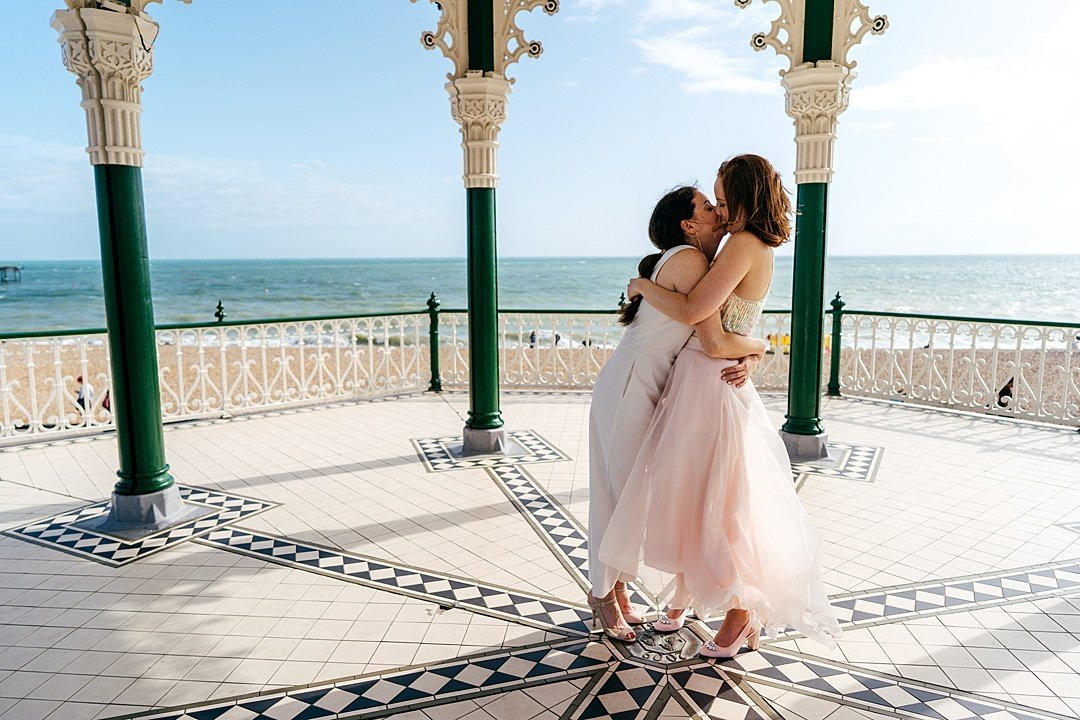 Brides kiss on Brighton Pavilion. Bride wears playsuit and sequined two piece