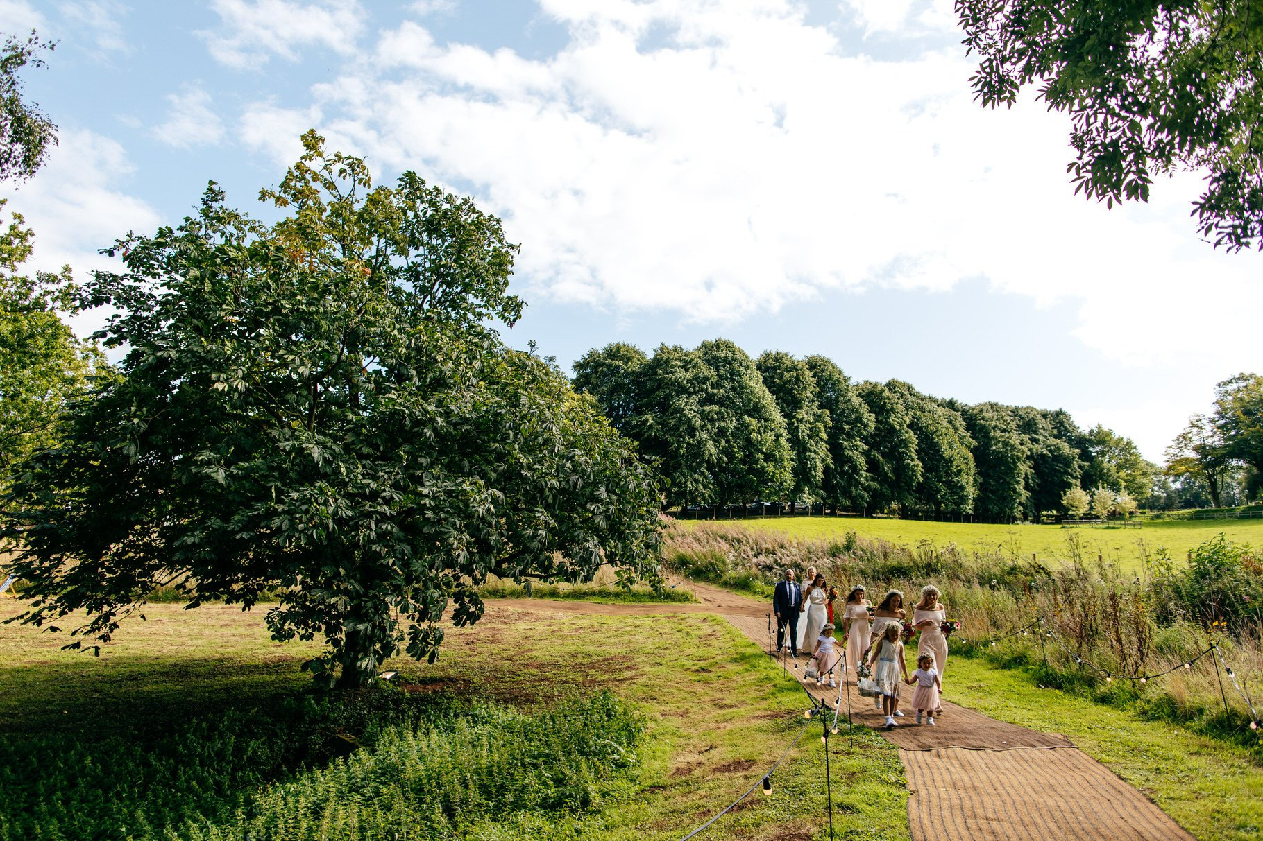 Bridal party walk down steep path way to wedding ceremony