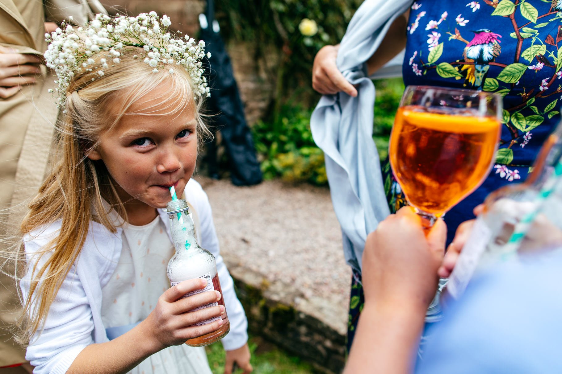 girl sipping drink at summer garden wedding