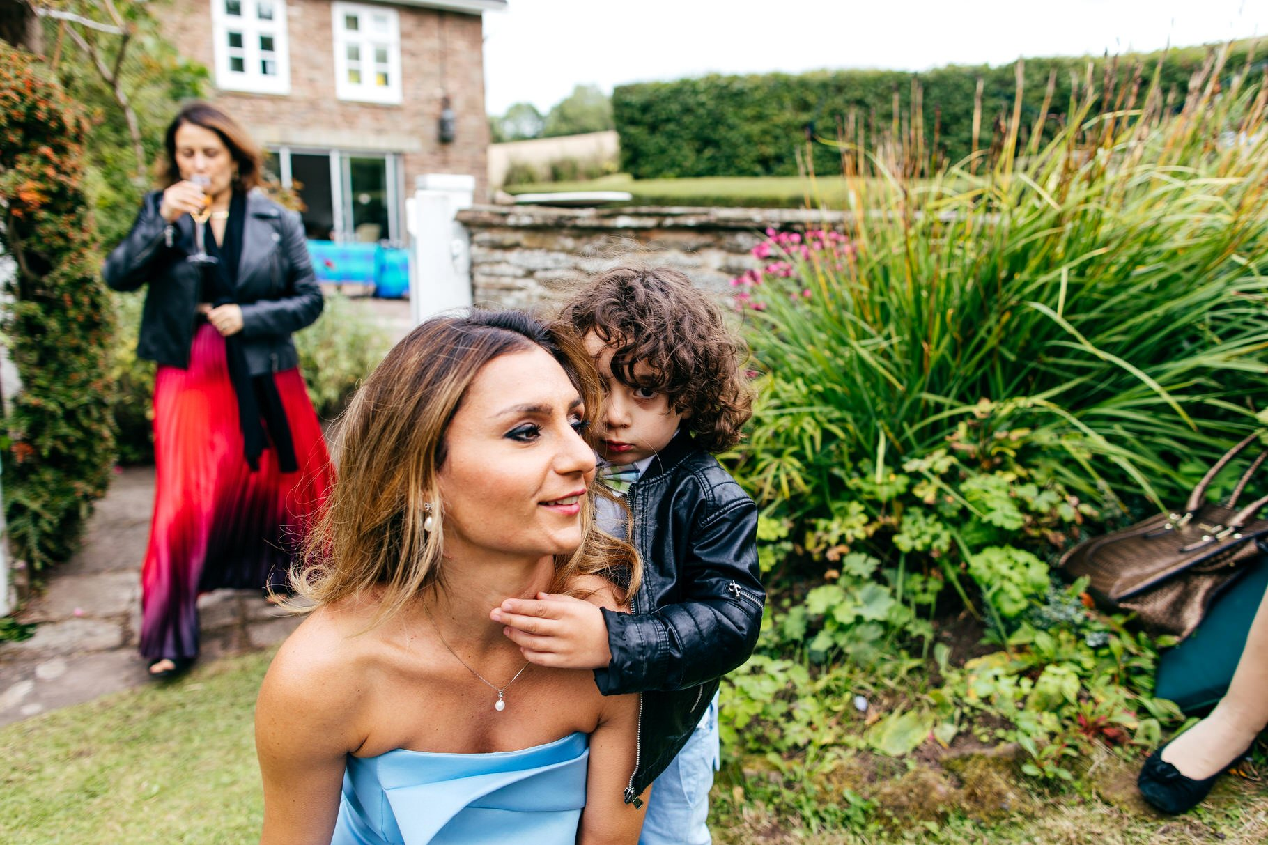 Shy child hiding behind his glamorous mum at wedding
