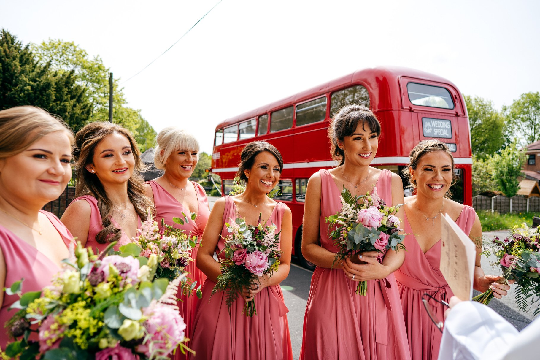 Bridesmaids in pink dress gather outside church in Manchester before Hope Mill Theatre Wedding