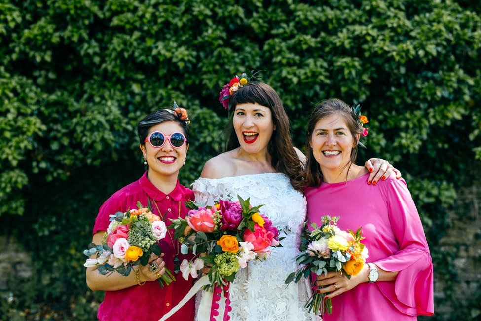Bride flanked by two super cool bridesmaids in shocking pink outfits with colourful wedding bouquets