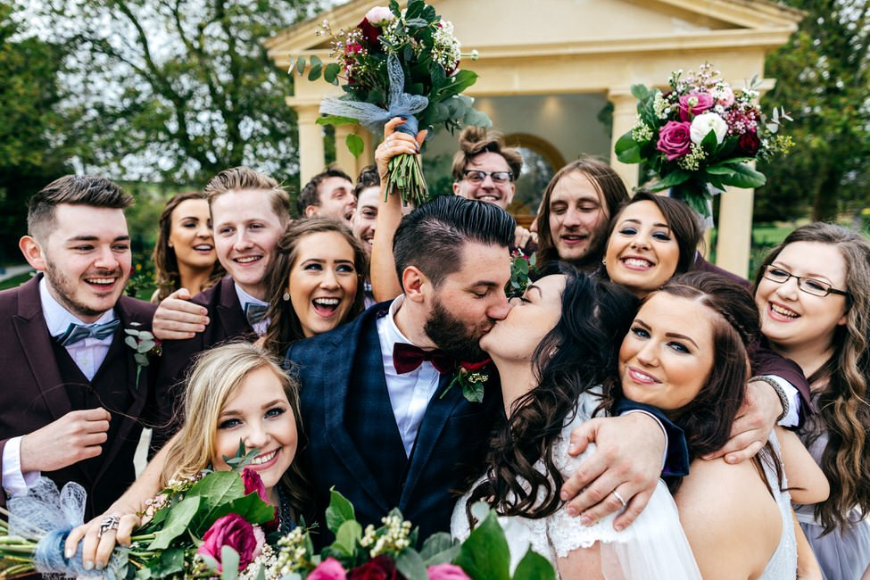Bride and groom kissing after ceremony at Rowton Castle surrounded by their bridal party