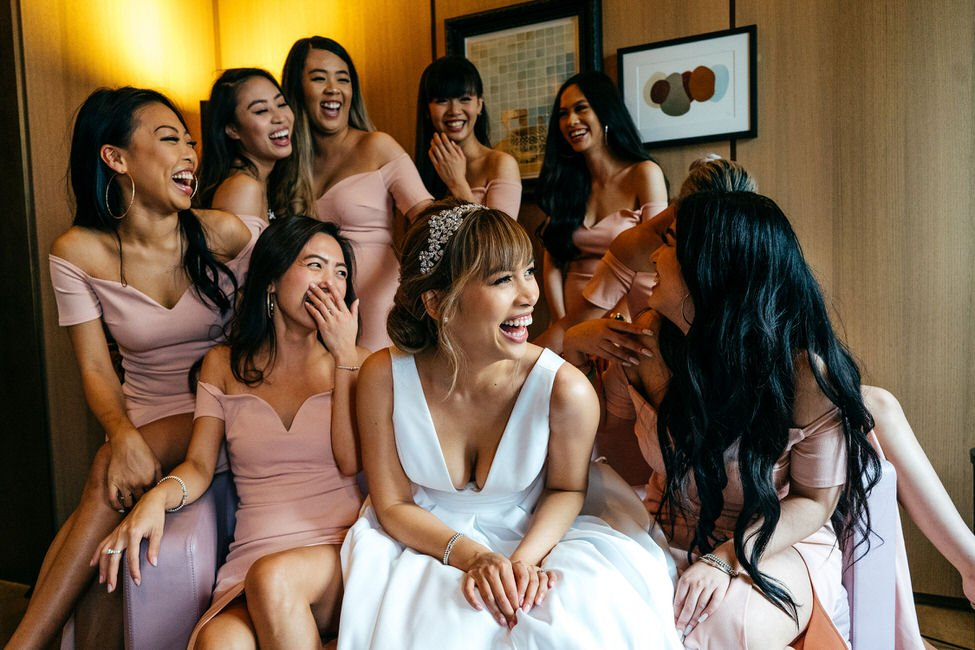 Bride and bridesmaids in Cafe Royal Hotel London sat around laughing