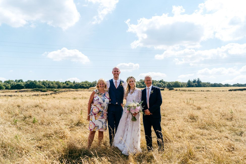 Bride, groom and brides parents get together for a family group shot in a field in Otley Leeds