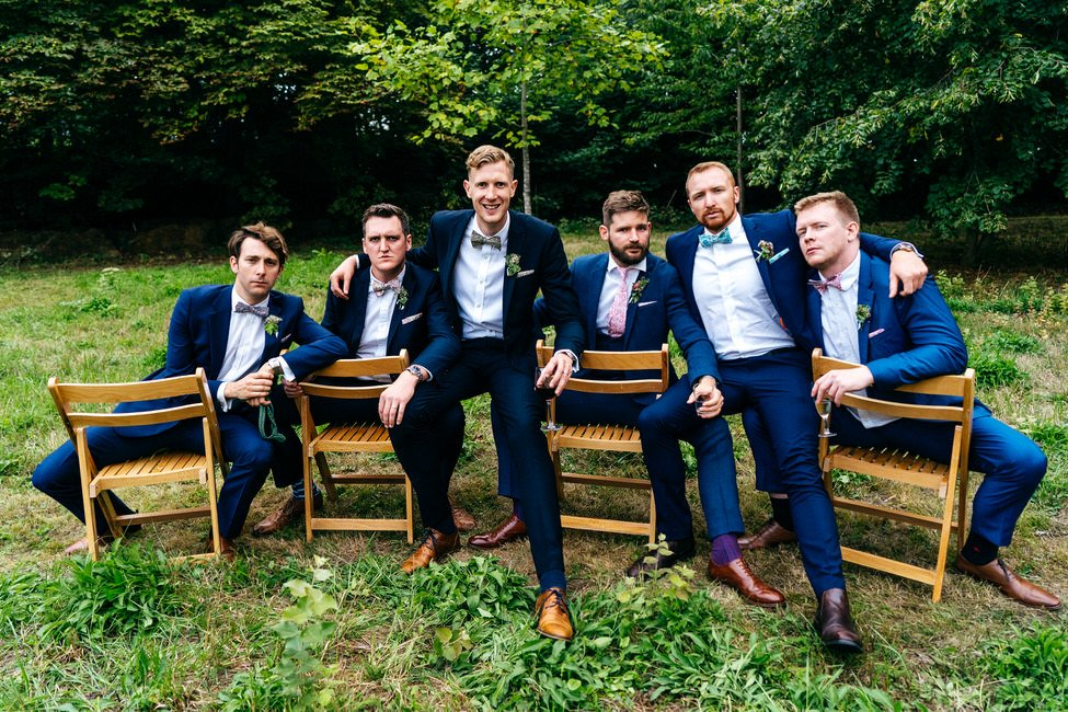 Groom and ushers in casual fun group shot sat on chairs backwards