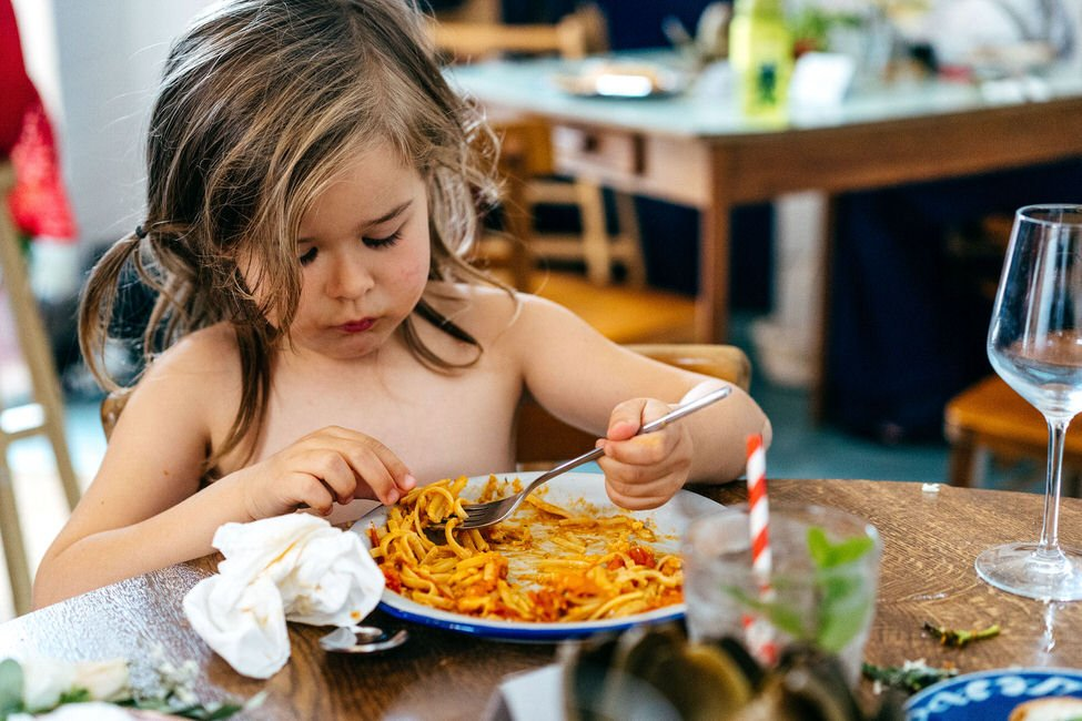 Girl eats her spaghetti with her bridesmaid dress off to prevent splashing on her white dress