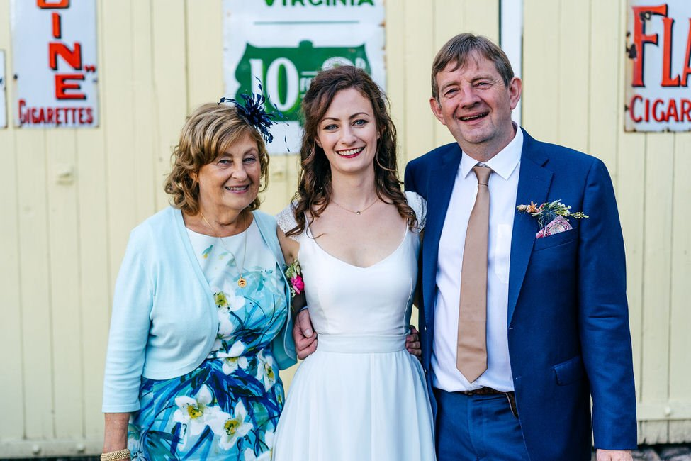 Simple family photo of bride and her mum and dad at disused railway museum