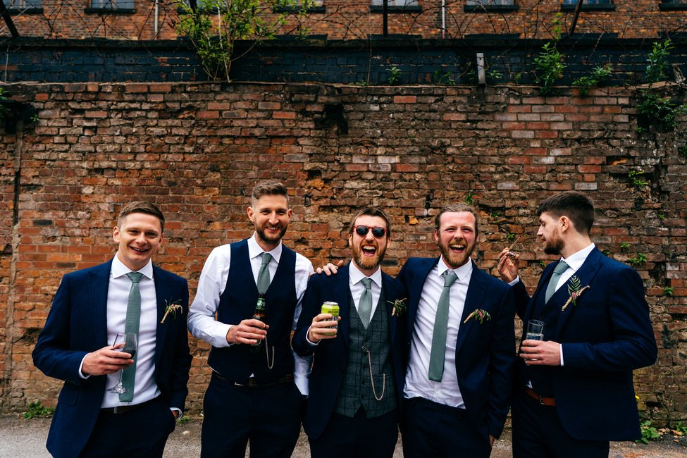 Lads line up at Hope Mill Theatre Wedding in Manchester laughing with beers in hand
