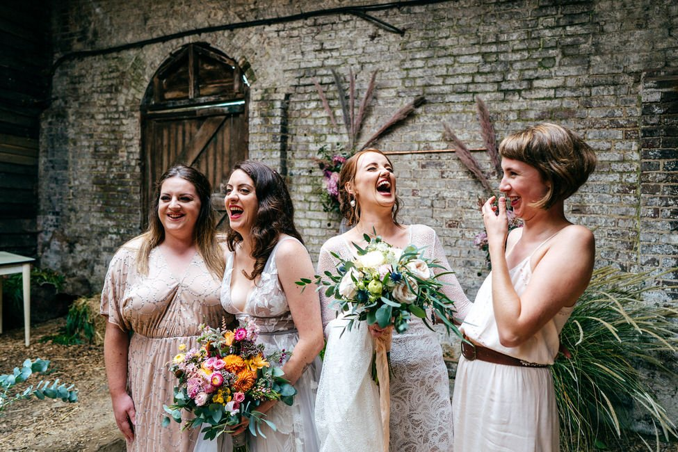 Two brides and best girls laughing in candid outtake during family group shot photos